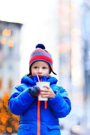 christmas in the city: little boy having hot drink in cold winter christmas city Stock Photo