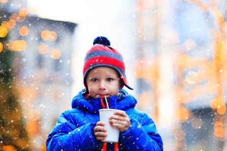 hot boy: little boy having hot drink in cold winter christmas city Stock Photo