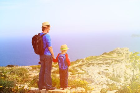 looking at baby: father and son travel in mountains, family travel