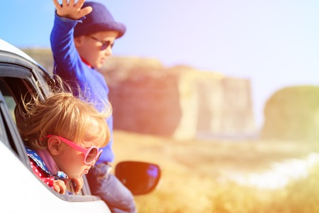 summer fun: happy little boy and girl travel by car in mountains, kids travel