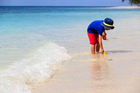 interst: little boy playing with paper boat at beach, kids beach activities