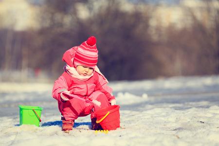 digging: little girl digging snow in winter, kids activities