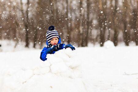 jungle boy: little boy building snowman in winter park Stock Photo