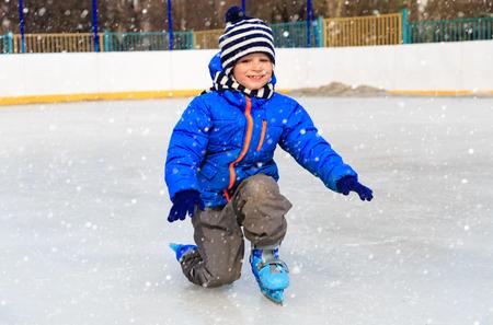 ni�o en patines: ni�o lindo aprender a patinar en la nieve del invierno Foto de archivo