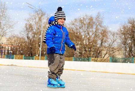 ni�o en patines: cute little boy learning to skate in winter snow