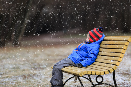 lonely boy: little boy sitiing on bench in winter park
