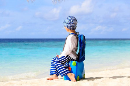 little boy travel on summer tropical beach with suitcase, kids travel Stock Photo