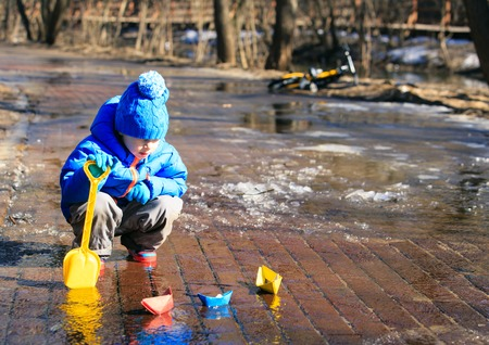 child playing with paper boats in spring water puddle