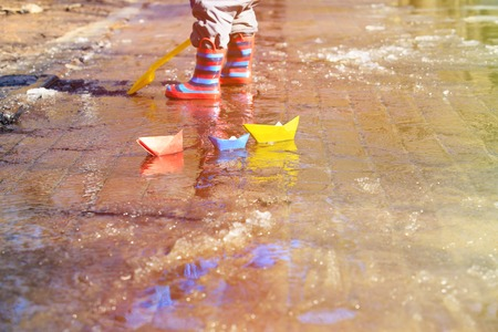 tar paper: child playing with paper boats in spring water puddle Stock Photo