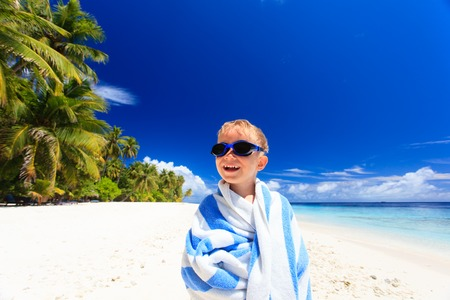 cool kids: happy little boy laugh wrapped in beach towel on sky