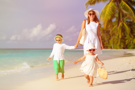 cute little girl walking on the beach with family on background