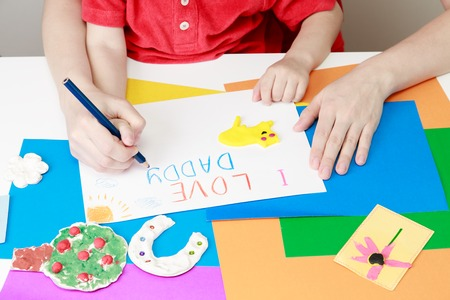 playdoh: mother and son drawing present for daddy, family love Stock Photo