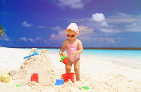 cute little girl building sandcastle on tropical summer beach