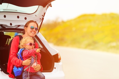 madre e hijos: mother and little daughter travel by car in summer nature