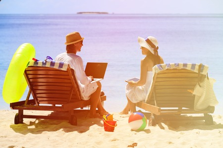 surfing the net: happy young couple surfing the net and enjoy beach vacation