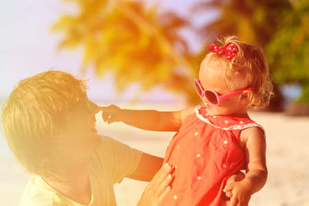 Happy father and cute little daughter play at tropical beach