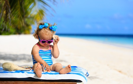 seashell: cute little girl listening to shell on beach, family vacation
