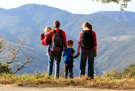 family with two kids hiking in mountains, active family