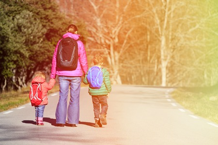 Mother And Two Kids With Backpacks Walking On The Road Stock Photo