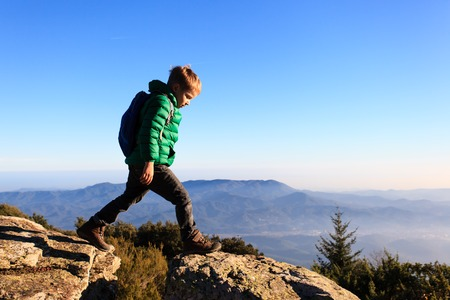 little boy with backpack hiking in scenic mountains, kids travel