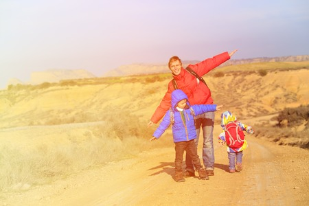 winter girl: father with kids travel on scenic road, family travel