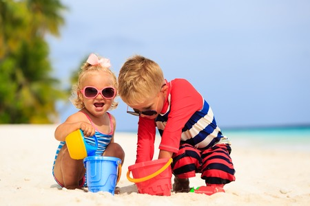 cute little boy and toddler girl play with sand on tropical beach