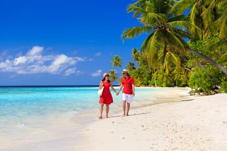white sand beach: happy loving couple walking on summer tropical beach Stock Photo