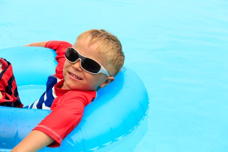 kids activities: little boy in life ring having fun in the swimming pool