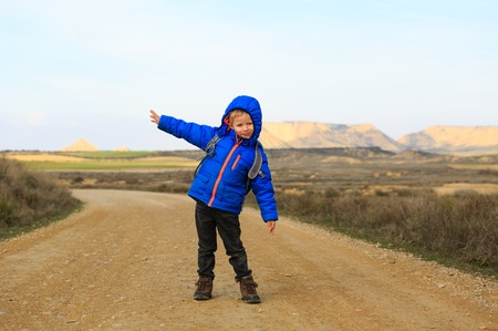 navarra: little boy with backpack travel on the road to scenic mountains