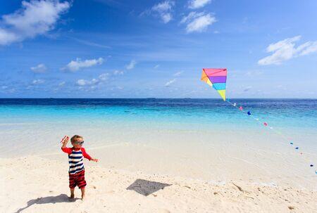 flying kites: Little boy flying a kite on tropical beach, kids beach activities Stock Photo
