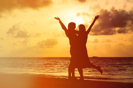 Happy young romantic couple on the beach at sunset Stock Photo