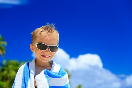 cool people: happy little boy laugh wrapped in beach towel on sky