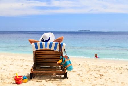 moeder ontspannen terwijl jongen spelen in water op het strand, familie vakantie