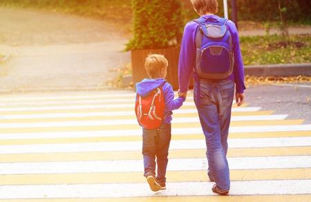 niños saliendo de la escuela: padre caminando pequeño hijo con la mochila a la escuela o guardería