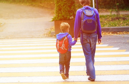father walking little son with backpack to school or daycare Stockfoto