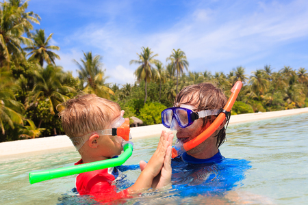 kid's day: happy father and son snorkeling on tropical beach