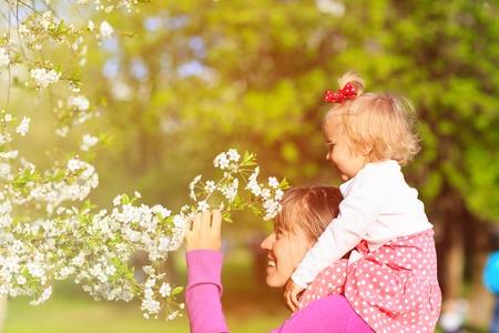 mother and little daughter enjoy spring blossom, spring concept