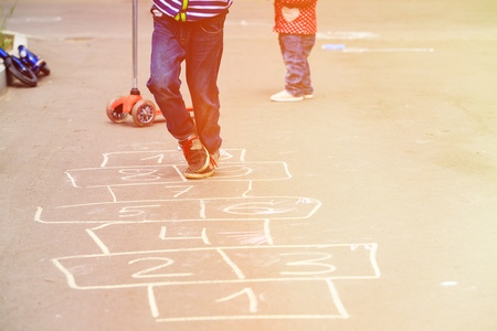 hopscotch: kids playing hopscotch on playground outdoors, children outdoor activities