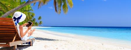 Mujer con la almohadilla táctil en la playa tropical de vacaciones, panorama