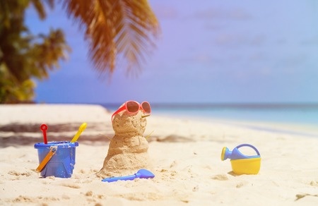 Sandy snowman and toys at sand tropical beach