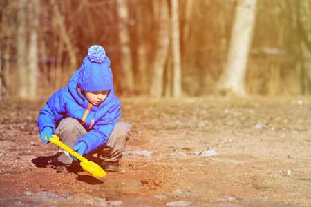 interst: little boy plaing in spring puddle, kids outdoor activities Stock Photo