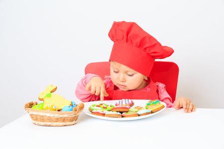 tradition: cute little girl playing with easter cookies, easter tradition Stock Photo