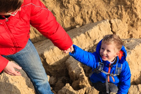 helping hand: Helping hand- little boy helped by parent on hiking in mountains Stock Photo