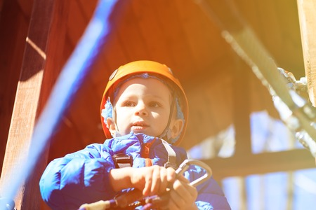 clambering: little boy climbing in adventure activity park with helmet and safety equipment