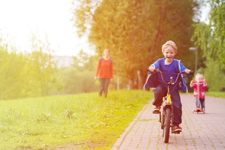 happy kids riding scooter and bike in the park, family sport