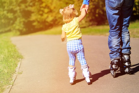 daugther: father teaching little daugther to roller skate, active family