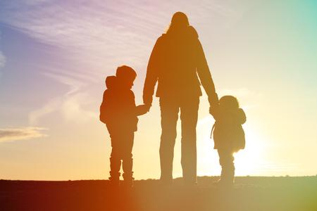 manos entrelazadas: madre y dos niños viajan al atardecer, turismo familiar