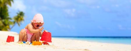 beach panorama: cute little girl play with sand on the beach, panorama