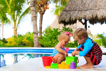 fun in the sun: little boy and toddler girl playing in swimming pool at beach