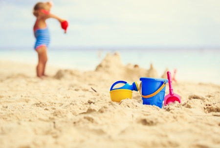 kids toys and little girl building sandcastle, family vacation Stockfoto